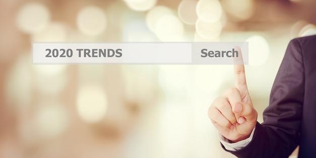 Ręka Biznesmena Dotykając Paska Wyszukiwania Trendów 2020 Ponad Rozmycie Biura Premium Zdjęcia