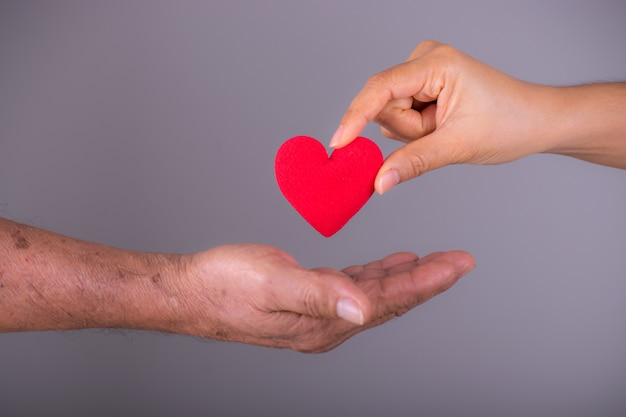 Ręka daje czerwone serce starszej ręce starszego. światowy dzień serca. Premium Zdjęcia