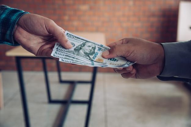 Ręka Daje Pieniądze - Dolary Amerykańskie. Ręka Odbiera Pieniądze Od Biznesmena. Pojęcie Korupcji Premium Zdjęcia