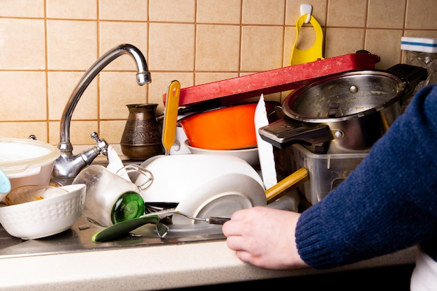 Ręka dziewczyny w pobliżu wielu brudnych naczyń leżących w zlewie w kuchni, które chcesz umyć Premium Zdjęcia