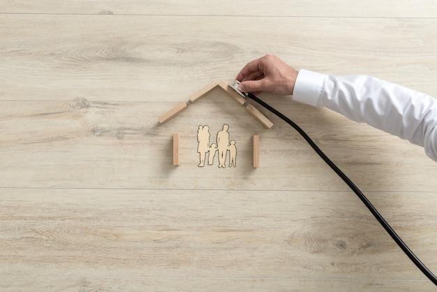 Ręka Eksperta Trzymającego Stetoskop Na Dachu Domu Rodzinnego. Premium Zdjęcia