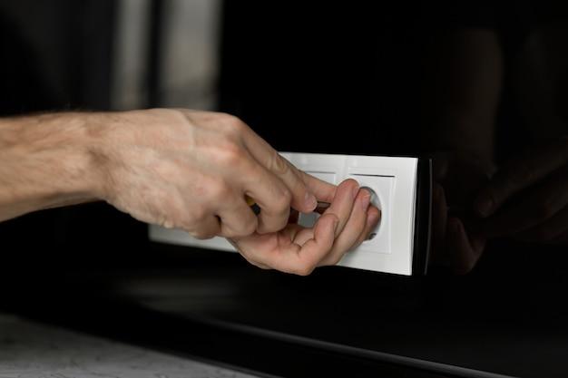 Ręka Elektryka Z śrubokrętem Demontującym Białe Gniazdko Elektryczne Na Czarnej Szklanej ścianie. Premium Zdjęcia