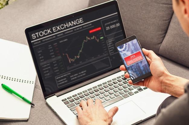 Ręka handlowa mienia telefonu komórkowego ekran dotykowy pokazuje kupować i sprzedawać na rynku papierów wartościowych Premium Zdjęcia