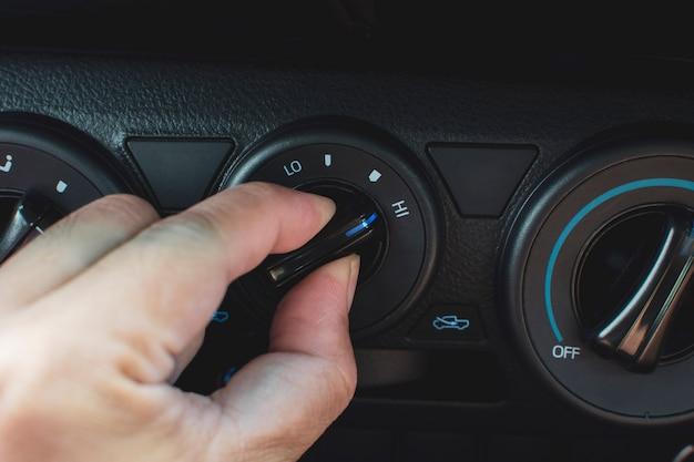 Ręka kierowcy reguluje przełącznik klimatyzatora w samochodzie, aby uzyskać wysoki poziom przepływu powietrza. Premium Zdjęcia