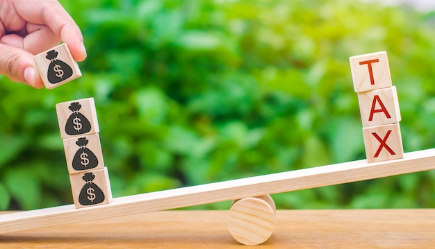 Ręka kładzie drewniane klocki. słowo podatek. Premium Zdjęcia