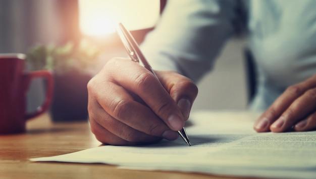 Ręka kobiety mienia pióro z pisać na papierowym raporcie w biurze Premium Zdjęcia