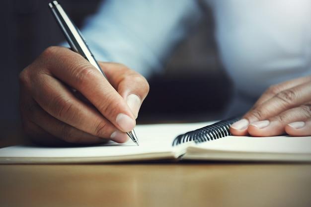 Ręka kobiety mienia pióro z writing na notatniku w biurze Premium Zdjęcia