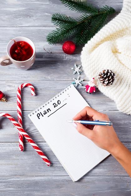 Ręka Kobiety Pisanie Na Notatniku życzenia Bożonarodzeniowe Z Herbatą, Dekoracja Na Drewnianym Premium Zdjęcia