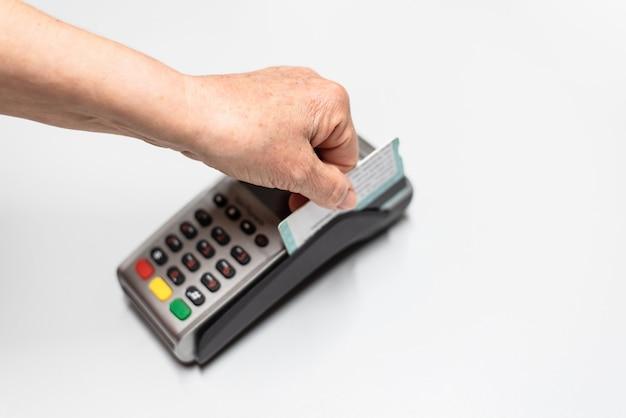 Ręka kobiety przekazanie karty kredytowej przez dataphone, czytnik kart do ładowania w czasie sprzedaży. Premium Zdjęcia