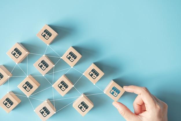 Ręka Kobiety Wybrać Blog Drewna Z Systemem Marketingu Franczyzy W Globalnej Sieci. Premium Zdjęcia