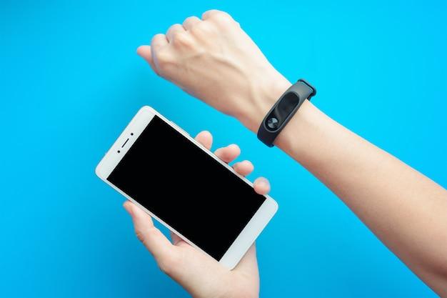 Ręka Kobiety Z Fitness Tracker I Smartphone Na Niebieskim Tle Premium Zdjęcia
