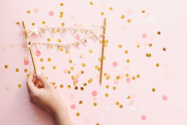 Ręka Kobiety Z Pastelowym Manicure'em Trzyma Mały Transparent Z Okazji Urodzin. Wszystkiego Najlepszego Pozdrowienia Na Różowym Tle Z Konfetti Premium Zdjęcia