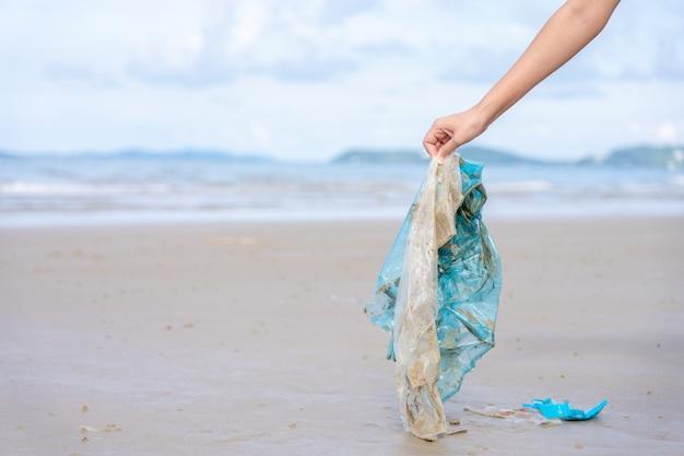 Ręka kobiety zbierająca używaną plastikową torbę na piaszczystej plaży Premium Zdjęcia