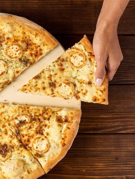Ręka Leżała Płasko, Biorąc Kawałek Pizzy Z Serem Darmowe Zdjęcia