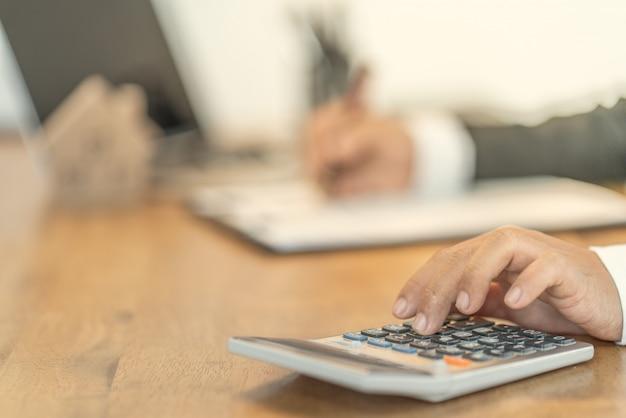 Ręka ludzi biznesu obliczająca odsetki, podatki i zyski w celu inwestowania w nieruchomości i kupowanie domów Premium Zdjęcia