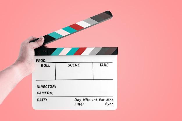 Ręka mężczyzna trzyma kinowego filmu łupek odizolowywający Premium Zdjęcia
