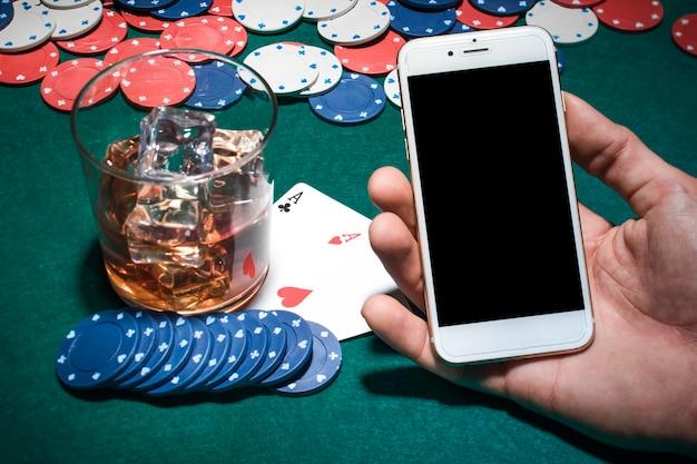 Ręka Mężczyzny Gospodarstwa Telefon Komórkowy Na Stole Do Pokera Z Kieliszkiem Whisky Darmowe Zdjęcia