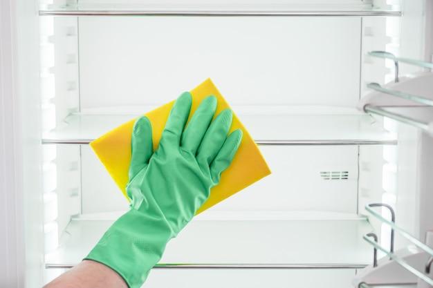 Ręka Mężczyzny W Zielonej Rękawicy Do Czyszczenia Pustej Lodówki Premium Zdjęcia