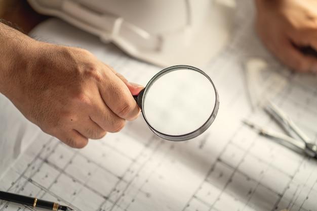 Ręka na szkło powiększające będzie jak koncepcja szacuje koszt budowy budynku Premium Zdjęcia
