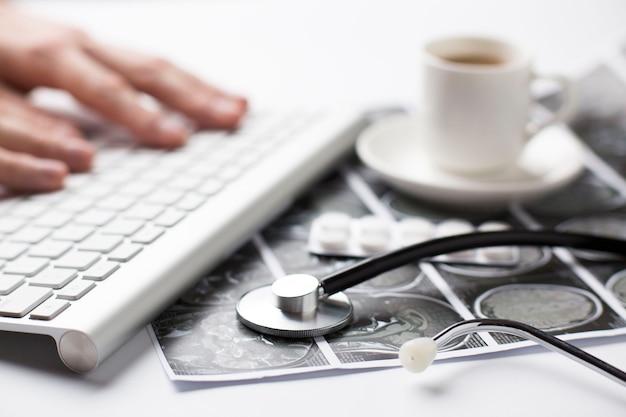 Ręka osoby wpisującej na klawiaturze w pobliżu raportu ze skanowania ultrasonograficznego; blister tabletek i filiżanka kawy na biurku Darmowe Zdjęcia