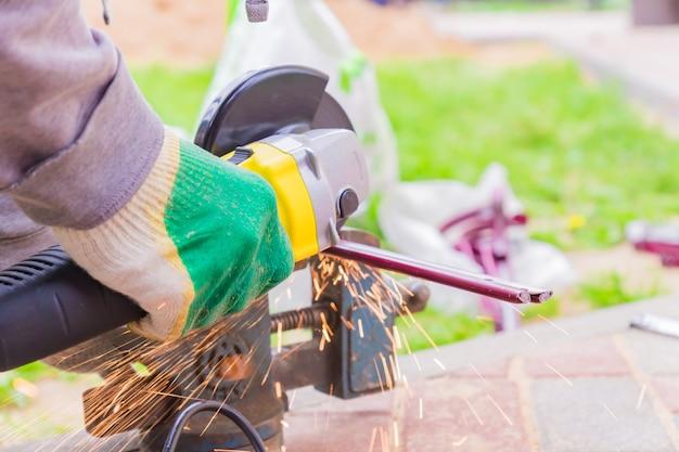 Ręka Pracownika Do Cięcia Metalu Za Pomocą Szlifierki. Iskry Podczas Szlifowania żelaza Premium Zdjęcia
