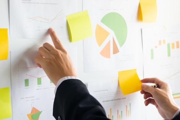 Ręka pracuje pieniężne dane i analizuje na wykresie biznes Premium Zdjęcia