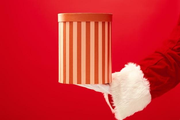 Ręka świętego Mikołaja Trzyma Prezent Na Czerwonym Tle. Sezon, Zima, Wakacje, Uroczystość, Koncepcja Prezentu Darmowe Zdjęcia