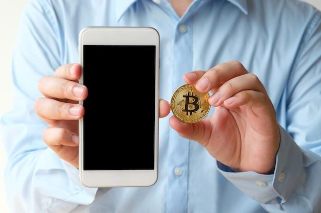 Ręka Trzyma Bitcoin I Smartphone Z Pustego Ekranu Tłem, Wyśmiewa Up, Cryptocurrency Premium Zdjęcia