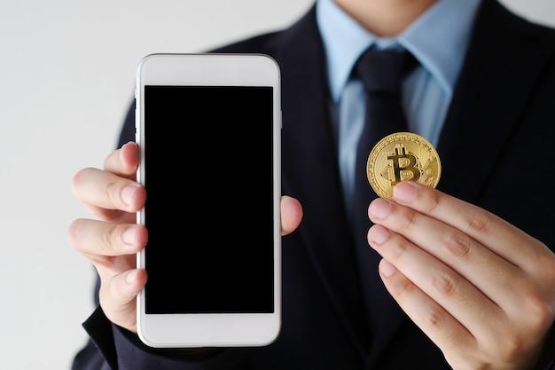 Ręka Trzyma Bitcoin I Smartphone Z Pustego Ekranu Tłem Premium Zdjęcia