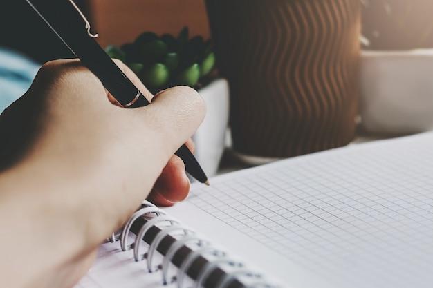 Ręka trzyma długopis i pisze w zeszycie Premium Zdjęcia