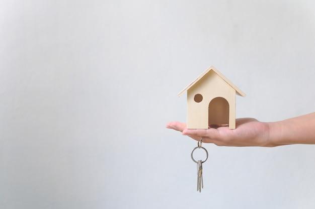 Ręka trzyma drewniany dom i dom pęku kluczy. inwestycje w nieruchomości i hipoteczne nieruchomości finansowe Premium Zdjęcia