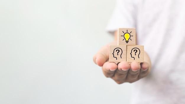 Ręka Trzyma Drewniany Sześcian Blok Z żarówką I Ludzkim Symbolem Głowy Premium Zdjęcia