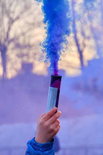 Ręka Trzyma Fajerwerki Z Dymem Koloru Niebieskiego. Premium Zdjęcia
