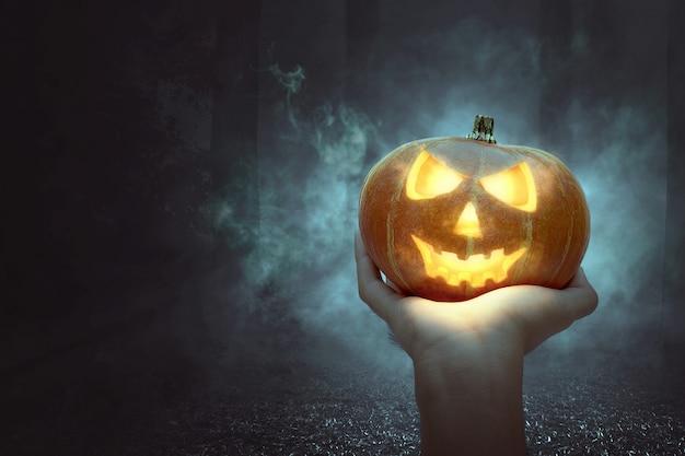 Ręka trzyma jack-o-lantern Premium Zdjęcia