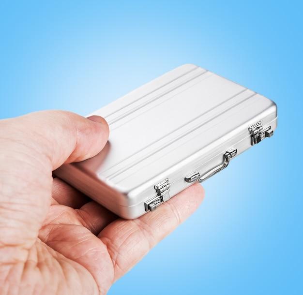 Ręka trzyma małą aluminiową obudowę Premium Zdjęcia