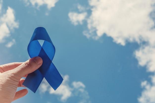 Ręka trzyma niebieską wstążkę, świadomość raka prostaty, świadomość zdrowotna mężczyzn, movember, międzynarodowy dzień mężczyzn, światowy dzień cukrzycy Premium Zdjęcia
