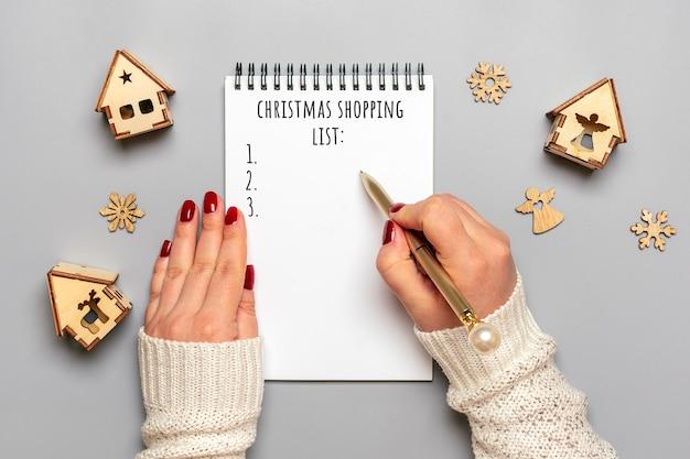 Ręka Trzyma Pióro, Pisanie Listy świątecznych Zakupów, Pomysły Na Prezenty Na Biały Notatnik Na Szaro Premium Zdjęcia