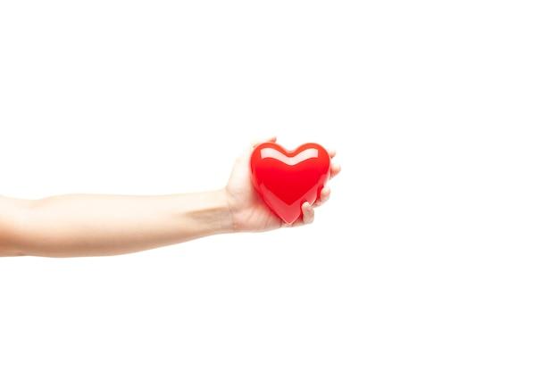 Ręka trzyma plastikowe czerwone serce na białym tle Premium Zdjęcia
