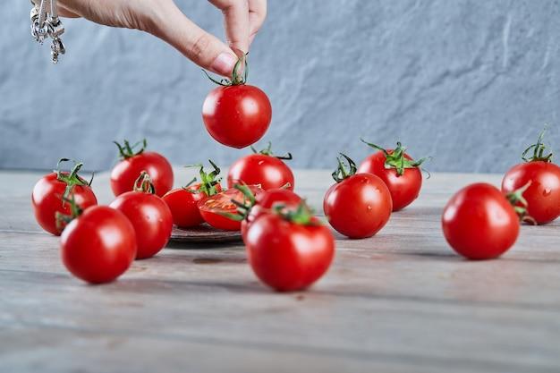 Ręka Trzyma Pomidora Z Bukietem Pomidorów Na Drewnianym Stole Darmowe Zdjęcia