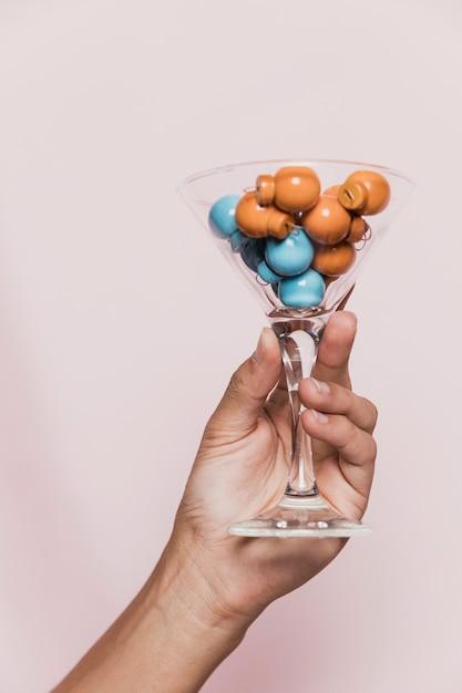 Ręka trzyma przezroczyste szkło z kolorowymi kulkami Darmowe Zdjęcia