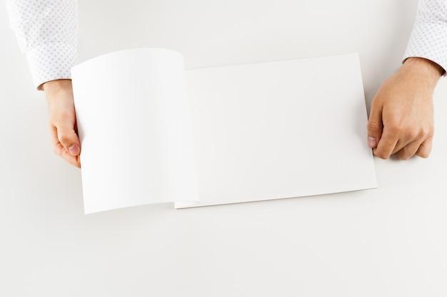 Ręka trzyma puste książki otwarte makieta Premium Zdjęcia