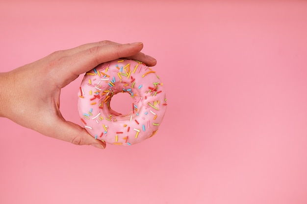 Ręka Trzyma Pyszny Pączek Na Różowym Tle Premium Zdjęcia