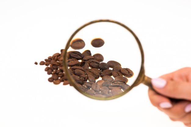 Ręka Trzyma Szkło Powiększające Nad Ziaren Kawy Darmowe Zdjęcia