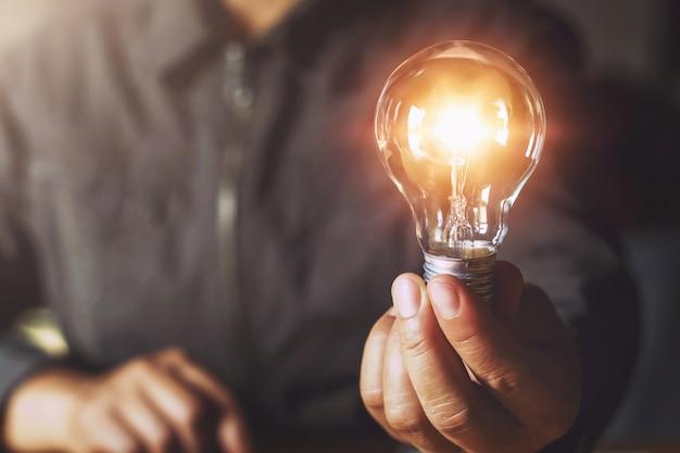 Ręka trzyma żarówkę. koncepcja pomysłu z innowacją i inspiracją Premium Zdjęcia
