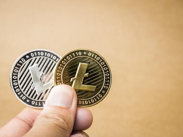 Ręka trzyma złote i srebrne monety litecoin. Premium Zdjęcia