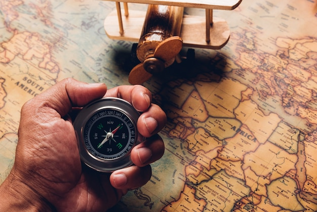 Ręka Trzymać Stary Kompas Odkrycie I Drewniany Samolot Na Mapie świata Antycznego Papieru Vintage Premium Zdjęcia