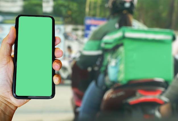 Ręka Trzymająca Smartfon Z Aplikacją Food Rozlany Kierowca Motocykla Pilnie Dostarcza Jedzenie Klientom, Którzy Zamawiają Online. Premium Zdjęcia