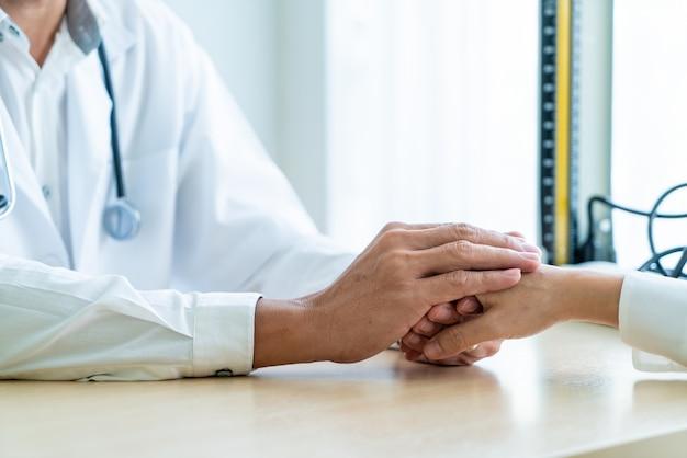 Ręka uspokaja jej żeńskiego pacjenta lekarka Premium Zdjęcia