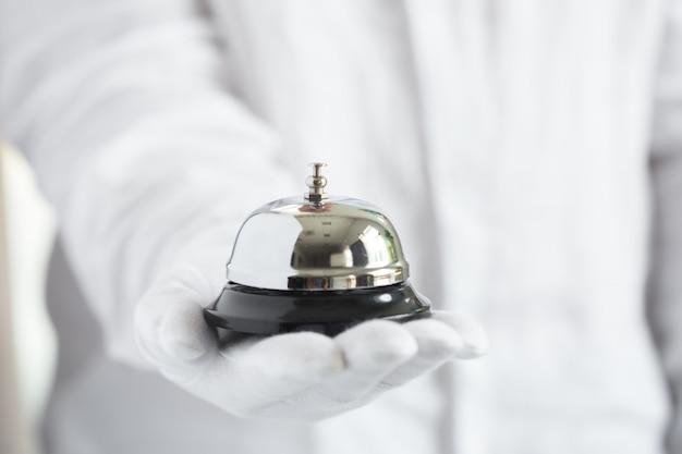 Ręka W Białych Rękawiczkach Trzyma Hotelowy Dzwon Premium Zdjęcia