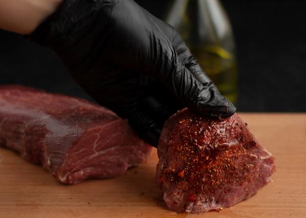 Ręka W Czarnej Rękawicy Trzymać Stek Wołowy Z Przyprawami Na Desce Premium Zdjęcia